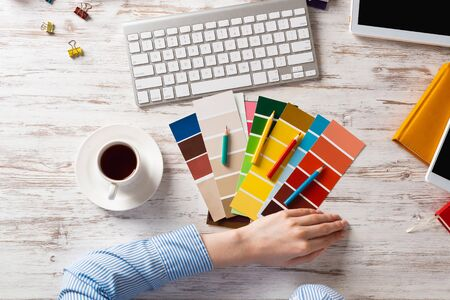 Web designer choosing colors from swatches at wooden desk. Office workplace with computer keyboard and cup of coffee. Designing user interface of mobile application. Coloristics in visual design.