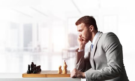 Businessman moving chess figure in chessboard. Successful management and leadership concept. Handsome man in business suit sitting at desk with chess. Operative tactics and strategy planning