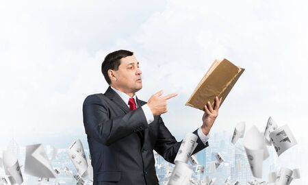 Senior businessman finger pointing into open book. Man in business suit and tie standing on cityscape background with falling paper documents. Manager holding handbook. Reference information concept