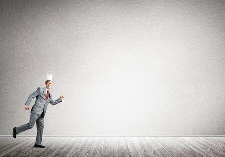 Młody przystojny biznesmen noszący białą papierową koronę biegnący w pośpiechu Zdjęcie Seryjne