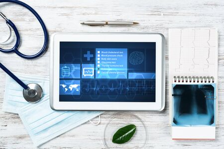 Modern social health insurance program. Tablet computer with healthcare application interface on screen. Stethoscope, x-ray image and cardiogram on wooden desk. Digital healthcare technologies. Фото со стока