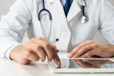 Close up of male doctor hands using tablet computer. Therapist in white medical gown with stethoscope sitting at desk. Modern technology in diagnosis and treatment. Medical digital application.