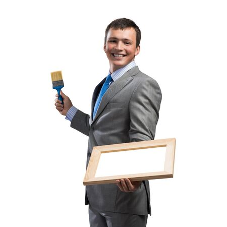 Creative businessman painter holding paint brush and whiteboard in hands. Portrait of happy handsome man in business suit and tie isolated on white background. Ambitions and creativity in business. 免版税图像