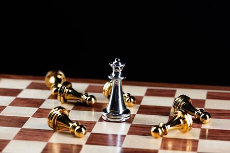 Silver queen chess defeats gold pawns on wooden chessboard. Intellectual duel and tactical battle in business. Strategy planning, leadership and teamwork. Checkmate and winning in game concept.