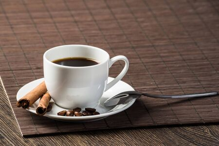 Strong natural coffee with spice on wooden table with bamboo mat. Coffee beans and cinnamon sticks on white porcelain saucer. Close up natural aromatic hot drink in restaurant. Morning coffee break.