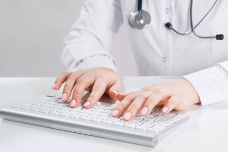 Close up doctor typing on computer keyboard. Female physician in white coat with stethoscope sitting at desk. Professional medical diagnosis and treatment in clinic. Healthcare and medicine.