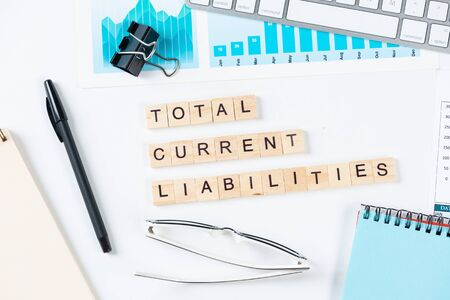 Total current liabilities concept with letters on cubes. Still life of office workplace with supplies. Flat lay white surface with notepad and financial analytics. Capital management and investment.