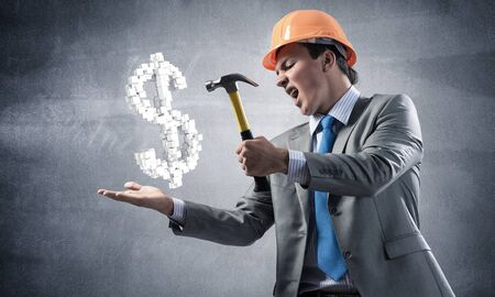 Furious businessman going to crash with hammer dollar symbol. Young handsome man in business suit and safety helmet standing on wall background. Financial crisis, bankruptcy and inflation pressure. 版權商用圖片