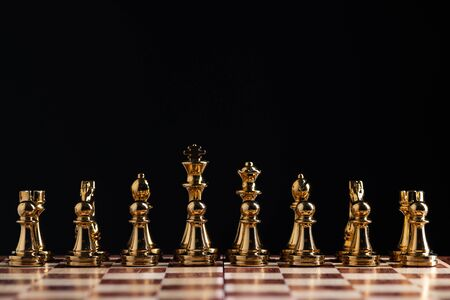 Golden chess figures standing on chessboard. Intellectual competition and fight in business. Strategy planning and leadership concept with copy space. Gold chess pieces in row on black background.