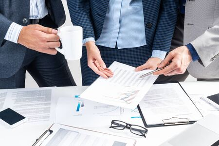 Corporate teamwork concept with business people. Idea presentation and strategy planning. Office desk with financial documents. Investment project analysis and discussion. Business meeting in office