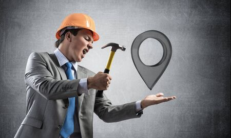 Furious businessman going to crash glass pin pointer symbol with hammer. Young man in business suit and safety helmet standing on wall background. Gps navigation service and system crush test.