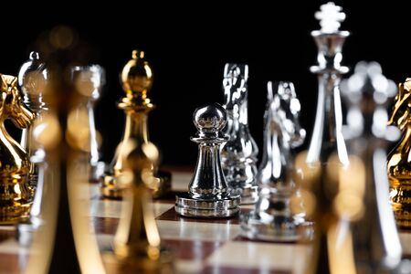 Gold and silver chess figures placed on wooden chessboard. Intellectual duel and tactical battle in business. Strategy planning, leadership and teamwork concept. Close-up metal chess pieces on board.