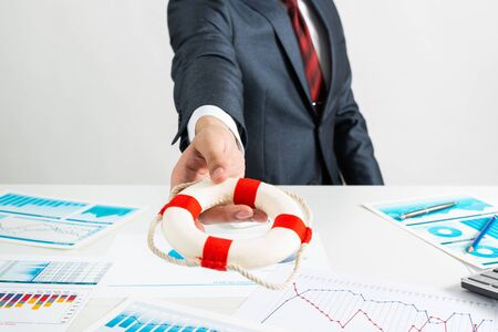 Consultant proposes lifebuoy as symbol of help. Business assistance and professional law consultation. Insurance services for business and life. Manager in suit and tie sits at desk in office. Banco de Imagens