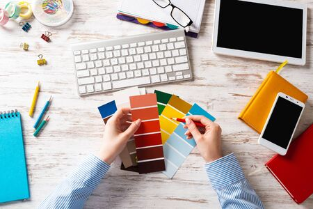 Interior designer choosing colors from swatches at wooden desk. Office workplace with computer keyboard. Selection of color palette for design. Professional house renovation and interior redesign.