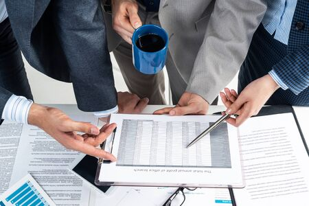 Company operational management and discussion of financial indicators. Corporate teamwork concept with business people in formal wear. Analysis of investment attractiveness and profit calculation.