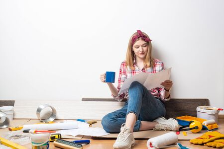 Beautiful girl sitting with paper blueprint in hand. Home remodeling and house interior redesign. Construction tools and materials lying on floor. Young woman studying renovation project of flat.