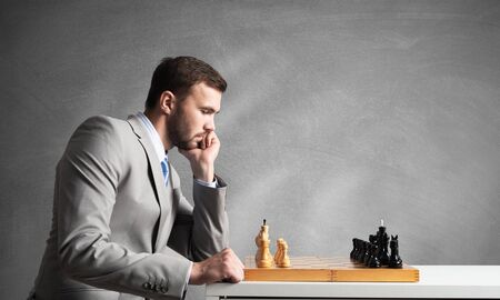 Businessman moving chess figure in chessboard. Successful management and leadership. Handsome man in business suit at desk with chess on grey wall background. Operative tactics and strategy planning.