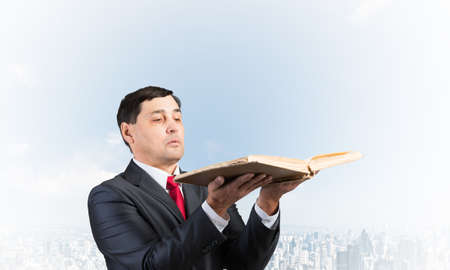 Serious businessman holding open old book. Adult man in business suit standing on cloudy cityscape background. Lawyer reading big legal regulation book. Professional business accounting and consulting
