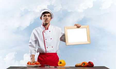 Young male chef standing near cooking table and holding blank white board. Handsome chef in white and red uniform on blue sky background. Cooking classes advertising. Professional catering service