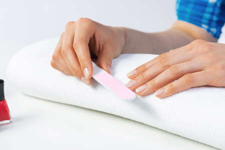 Woman hand using nail file and create perfect nails shape. Closeup grinding female nails with nail file. Woman doing herself nail care procedure at home. Natural beauty and hygiene concept