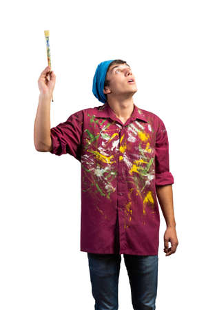 Smiling young painter artist pointing upwards with paintbrush in hand. Portrait of happy painter isolated on white background. Creative hobby and artistic occupation. Art school student posing. 写真素材