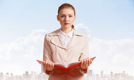 Attractive woman holding open notebook on background of cityscape and blue sky. Elegant young woman in white business suit with open book in hands. Internship and practice in company.