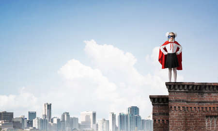 Young girl in superhero costume standing on building roof. Mixed media Stock fotó - 150644849