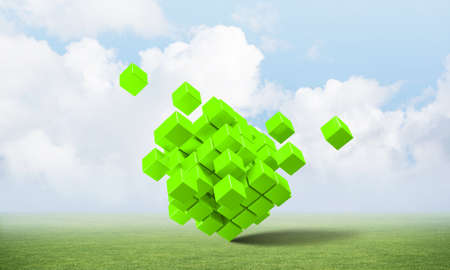 Abstract green cubes on green meadow. Digital technology and innovation solutions. New approach to business management. Nature landscape with green grass and blue sky. Mixed media with 3D object Stock Photo