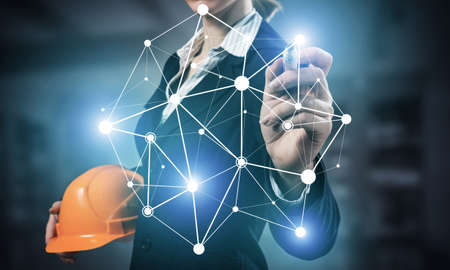 Businesswoman pointing on abstract 3d network. Woman engineer in business suit holding safety helmet. Engineering and project management. Social connection and networking concept with plexus structure Stok Fotoğraf