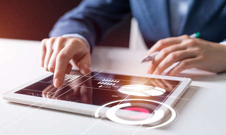 Businessman hand touching virtual screen flying above digital tablet. Online project management and financial diagrams visualization. Modern business innovation and intelligence technology.