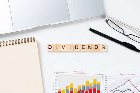 Dividends payment concept with letters on wooden cubes. Still life of office workplace with supplies. Flat lay white surface with laptop, notepad and financial report. Capital savings and investment