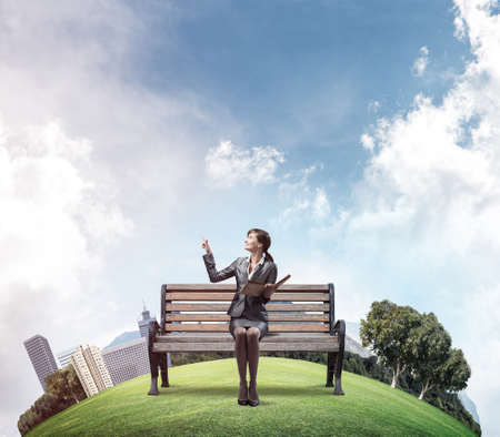 Young woman holding open book and sitting on wooden bench outdoors. Beautiful girl in business suit finger pointing in sky. City panorama with round horizon. Business education and knowledges