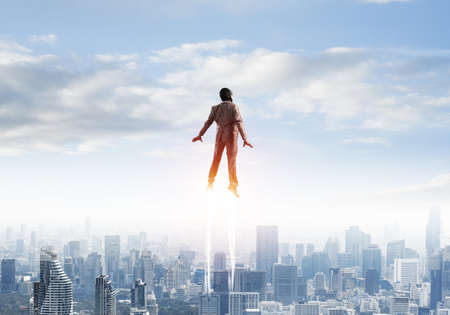Businessman in suit and aviator hat flying in blue sky as superhero. Back view of corporate manager as superhero launching upwards with jet flame above modern city. Successful business startup