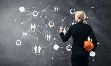 Businesswoman designing social network interaction structure. HR specialist in business suit with safety helmet. Recruitment agency presentation. Human resource management and career development. Stok Fotoğraf