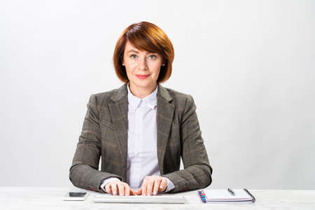 Business woman typing on computer keyboard. Concentrated accountant sitting at desk on white wall background. Successful corporate woman in suit posing at workplace. Professional occupation in office.