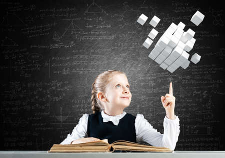 Smiling little girl sitting at desk with open book. Research and education in school. Happy schoolgirl in school wear finger pointing on 3d cubes. Clever girl reading book on chalkboard background.