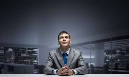 Young smiling man folded hands and looking upward. Happy businessman sitting at desk and dreaming about something good. Portrait of guy wears business suit and tie in conference room. 免版税图像 - 150645083