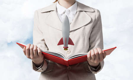 Woman showing rocket ship on open book. Rocket launch as symbol startup company. New creative project concept. Woman in white business suit on background of skyscape. Business innovation. Imagens