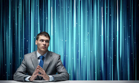 Young specialist in business suit and tie sitting at desk. Digital technology for business. Man on abstract digital backdrop. Human resources in modern internet company. Headhunting and hr managment Reklamní fotografie