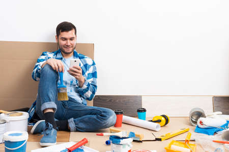 Smiling man surfing internet on mobile phone while sitting near wall. House remodeling and interior renovation. Young bearded guy sitting on floor among cardboard boxes and painting tools at home.