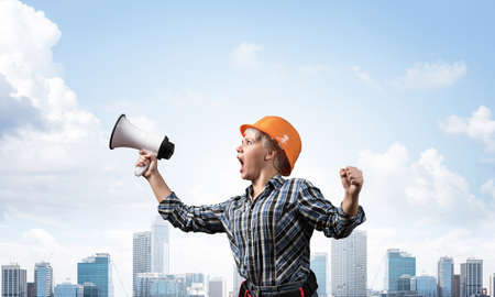 Expressive woman in safety helmet shouting into megaphone. Portrait of young emotional construction worker with wide open mouth on background of modern city. News announcement and advertisement.