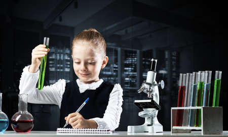 Little girl scientist with test tube writing in notebook. Research and education in school. Chemical laboratory with microscope and glass flasks. Schoolgirl making experiment in chemistry class.