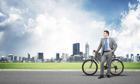 Young man wearing business suit and tie standing on asphalt road with bike. Businessman with bicycle on background of business center. Outdoors male cyclist holding bicycle, having break in riding. Stock Photo