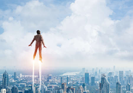 Businessman in suit and aviator hat flying in blue sky as superhero. Back view of corporate manager as superman launching upwards with jet flame above modern city. Successful business startup Imagens