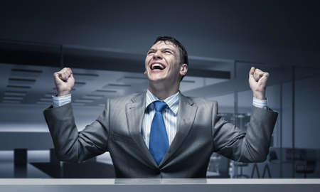 Happy excited businessman celebrating victory in business. Businessman feeling satisfaction from win. Portrait of guy wears business suit and tie in conference room. Personal success and triumph