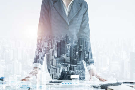 Businesswoman in suit standing near office desk with financial charts. Meeting in conference room. Business idea presentation, analyze and strategy planning. Entrepreneurship double exposure concept