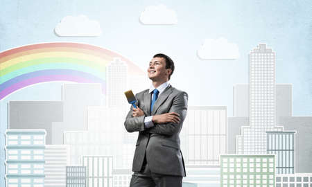Confident and creative businessman painter standing with arms folded. Happy handsome man in business suit and tie holding paintbrush on city background. Cityscape illustration with rainbow.
