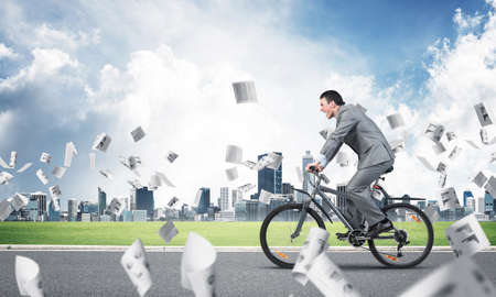 Accountant wearing business suit riding bicycle on road under falling commercial documentation. Financial statistics and analytics. Businessman hurry to work by bike. Cyclist on background of blue sky Stock Photo
