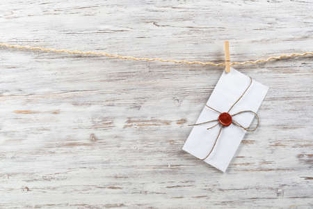 White classic envelope hanging on twine rope with clothespins. Vintage declaration of love on wooden painted background. Retro letter envelope with sealing wax stamp. Romantic wedding invitation. Imagens
