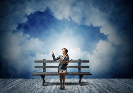Young woman holding open book on wooden bench outdoor. Beautiful girl in business suit finger pointing in night sky. Skyscape with deep blue night sky. Business education and knowledge.